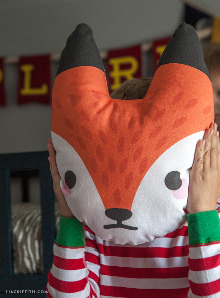 kid holding fox pillow in front of his face