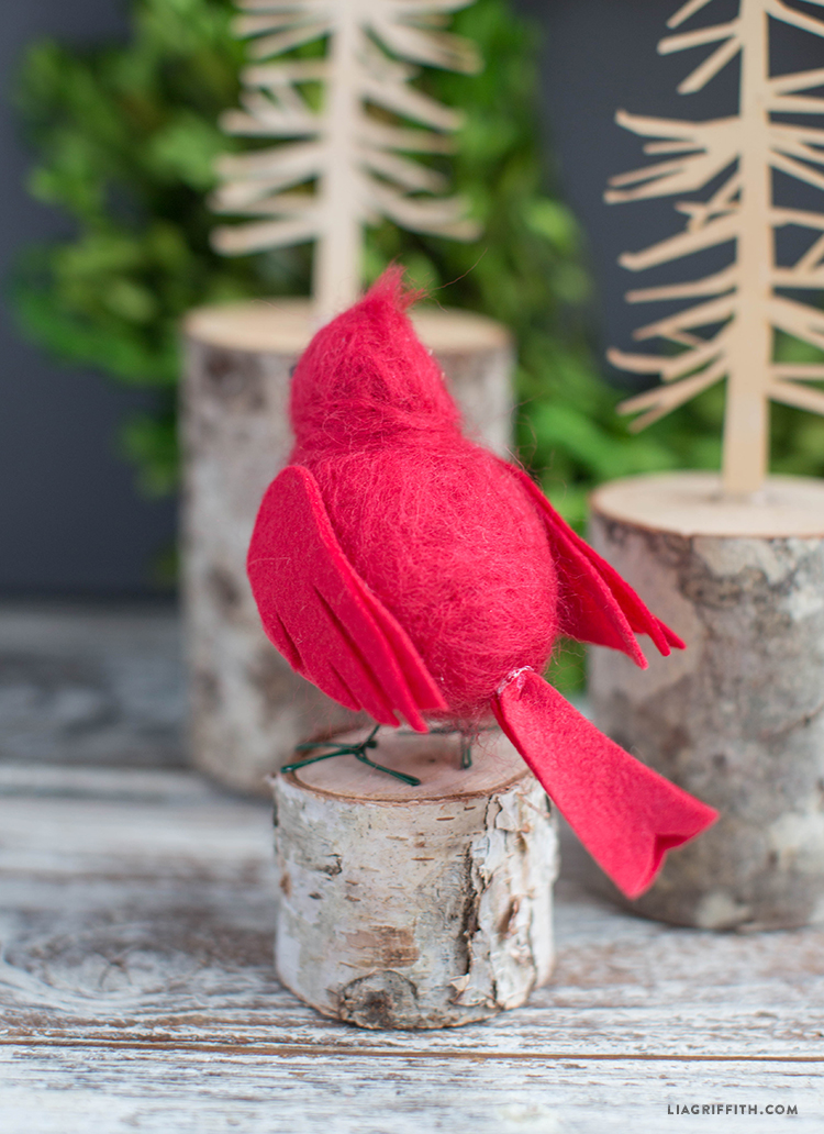 Red felted cardinal bird standing on wood slice