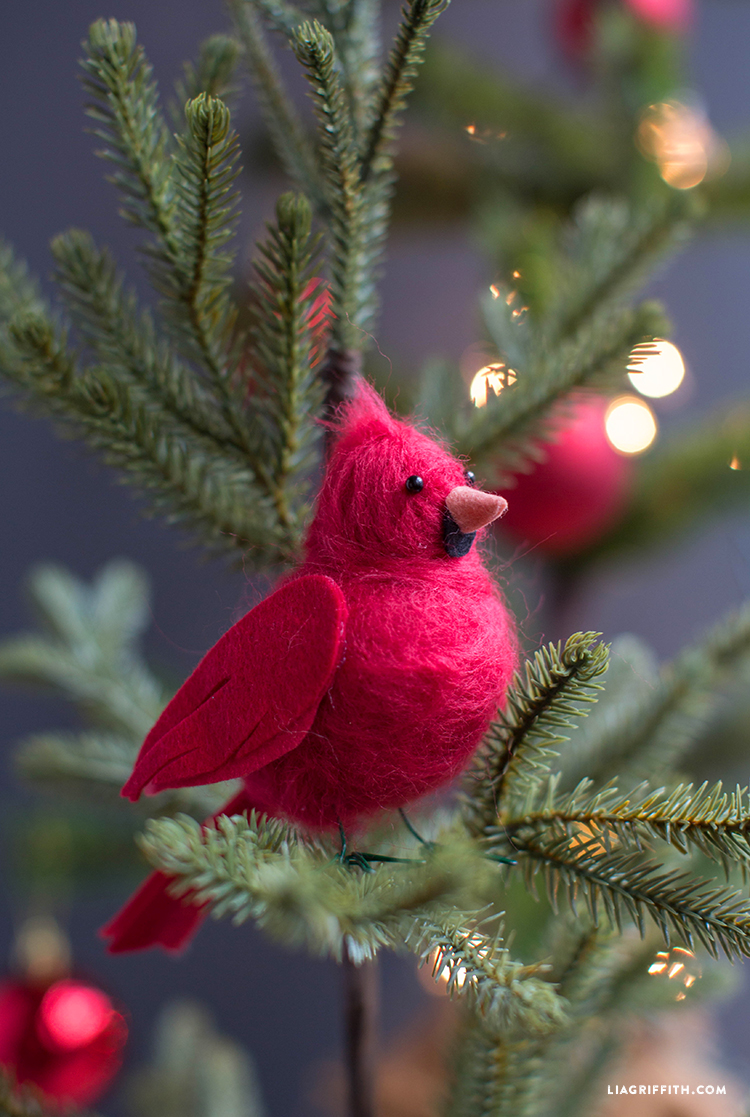 Red felted cardinal bird perched on Christmas tree