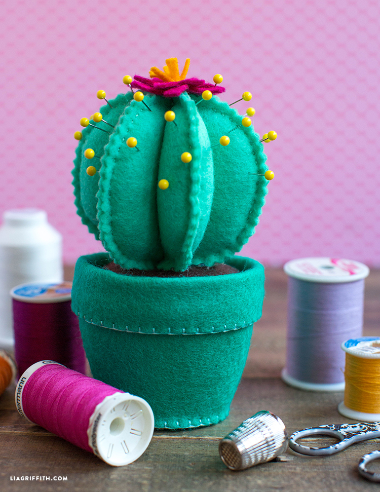 felt cactus pincushion next to spools of thread