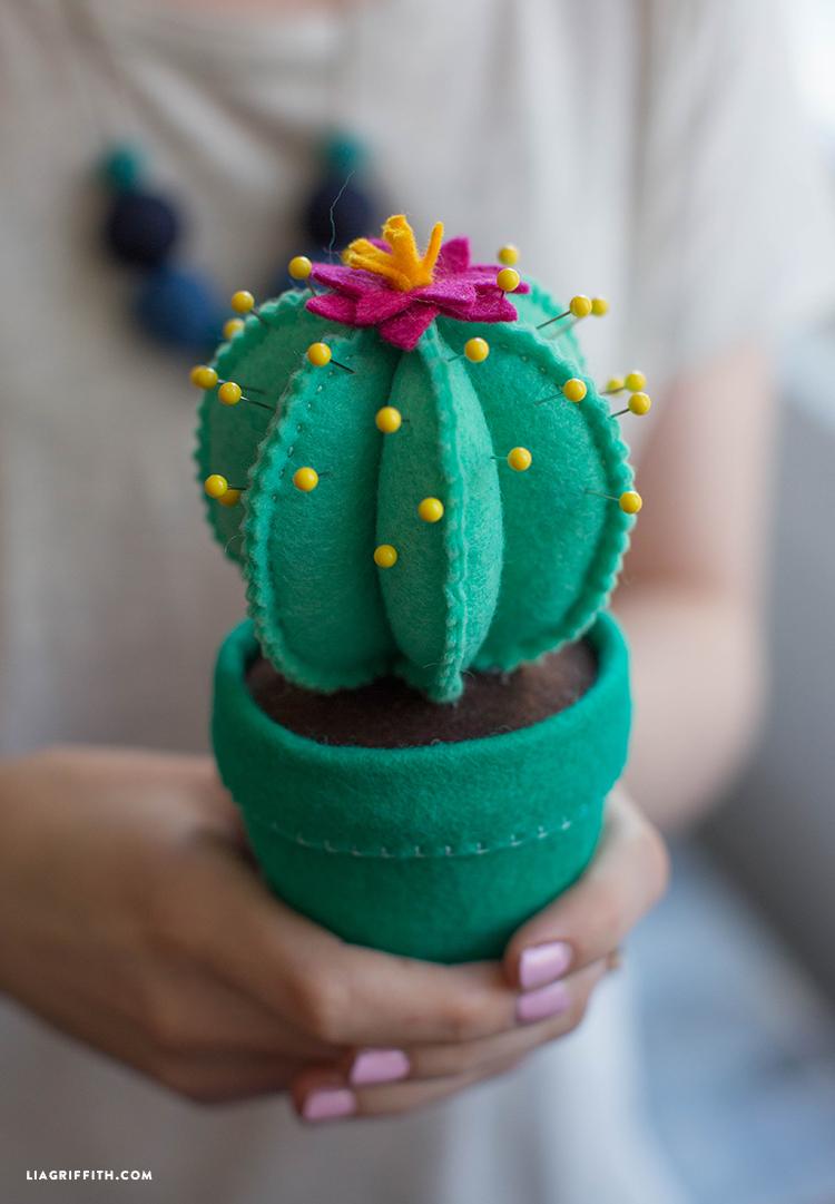Person holding felt cactus pincushion