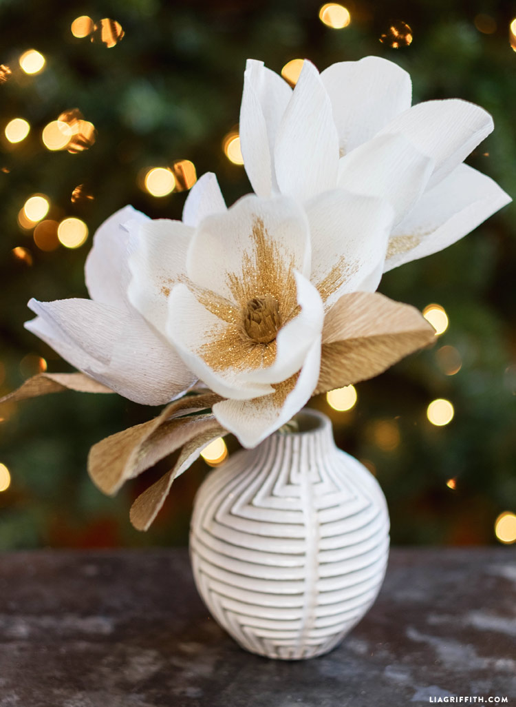 crepe paper magnolia blooms in white vase with lit-up tree in background