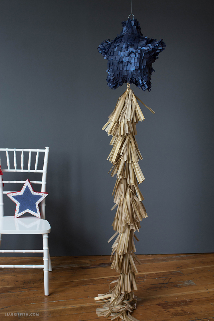 DIY tissue paper star piñata with gold tassel next to white chair with star on it
