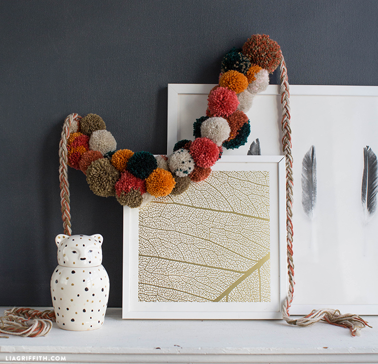 Fall pom-pom garland hanging on framed art on mantel