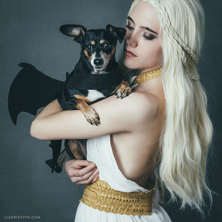 Woman holding dog in dragon costume