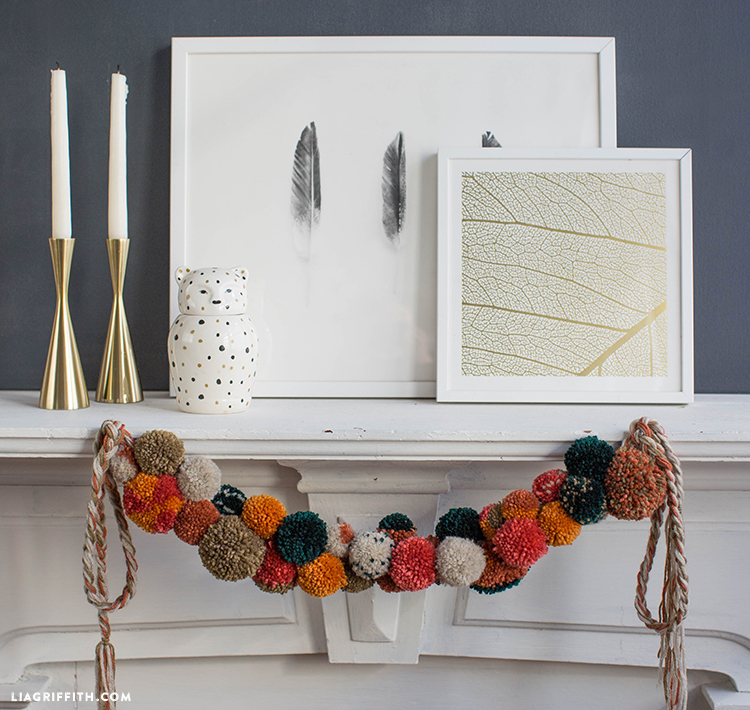 Fall pom-pom garland hanging on front of mantel