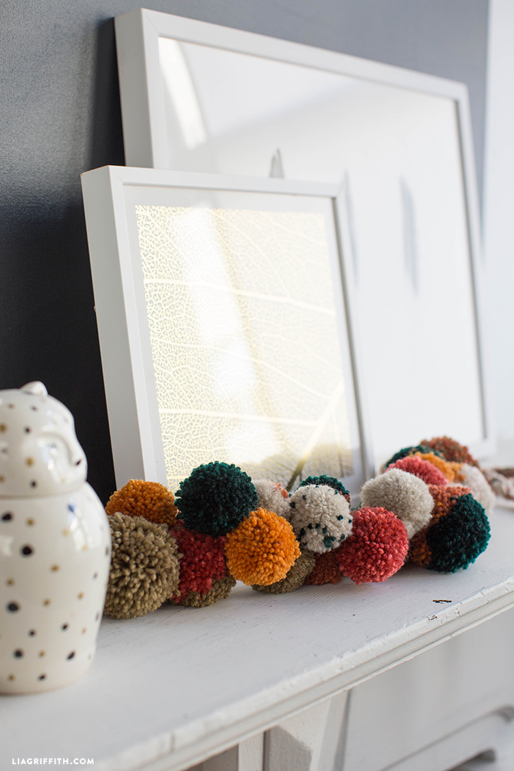 Fall pom-pom garland on mantel next to framed art