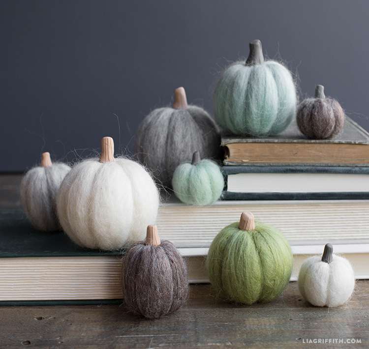 a collection of needle felted pumpkins on books