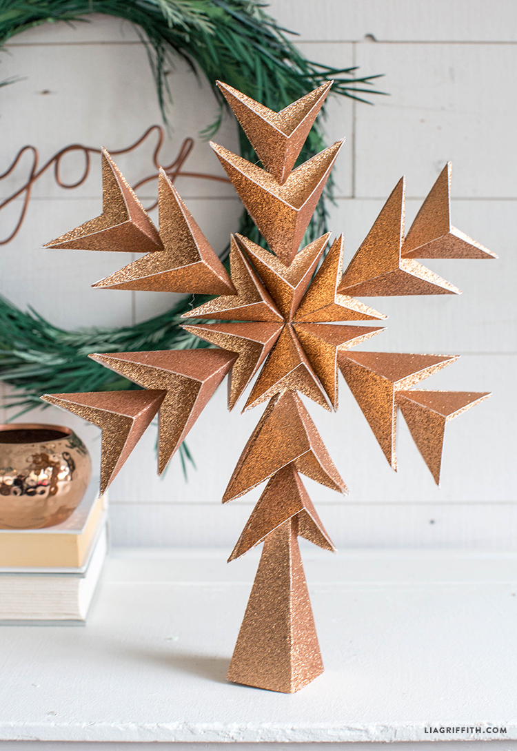 glitter paper star tree topper next to DIY holiday wreath