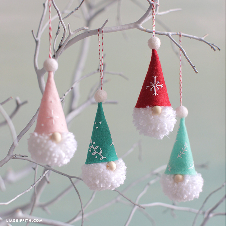 pom-pom gnome ornaments hanging on white banches