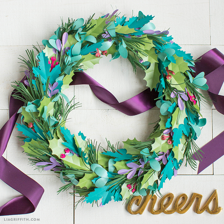 "DIY holiday wreath with purple ribbon through it and gold ""cheers"" below"