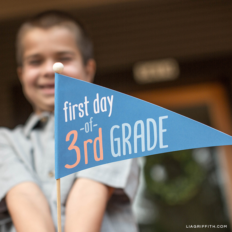 Boy holding first day of 3rd grade pennant flag