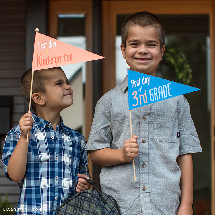 Boy holding first day of kindergarten pennant flag and boy holding first day of third grade pennant flag