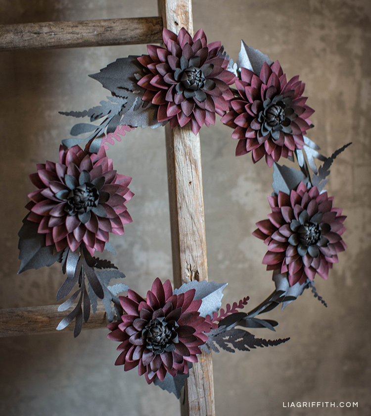 Black and purple paper dahlia wreath hanging on wood ladder