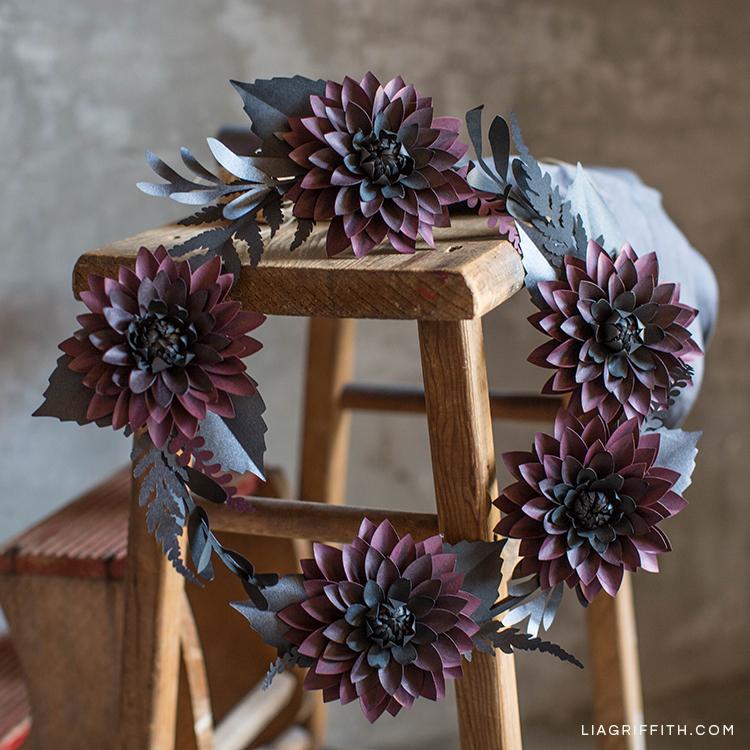 Black and purple paper dahlia wreath hanging on wood stool