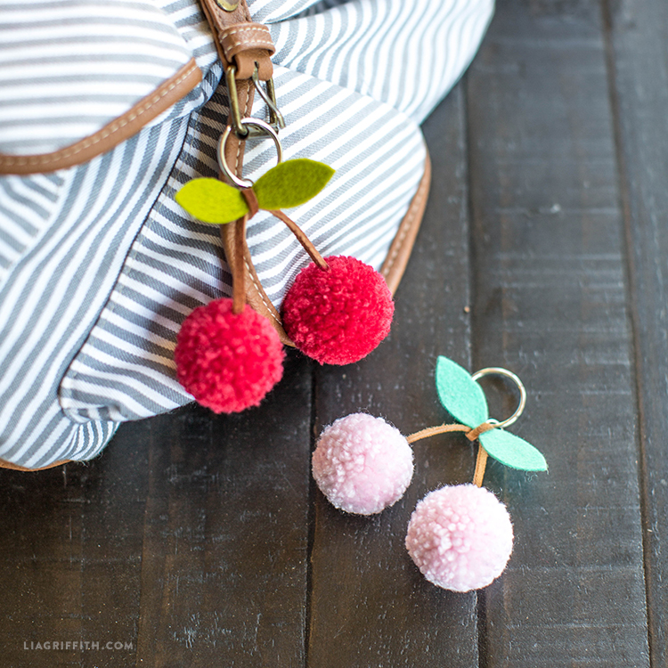 Red cherry pom-pom keychain on backpack and pink cherry pom-pom keychain on table