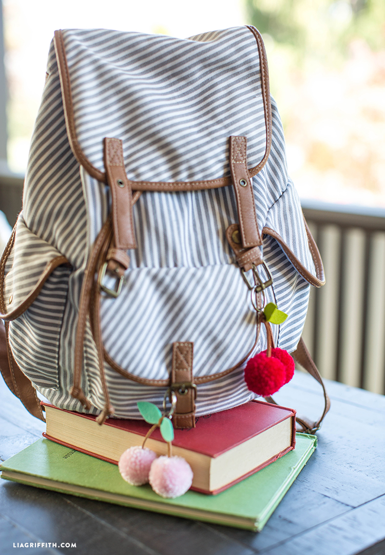 Two books and backpack with cherry pom-pom keychains