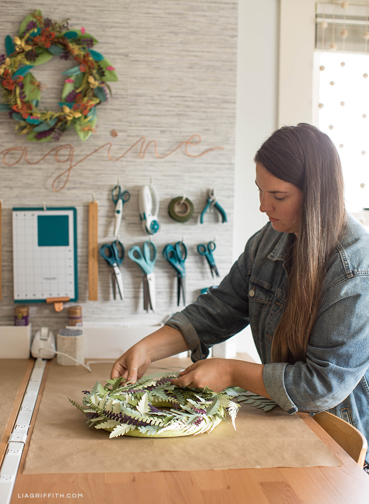 Designer making paper wreath at new craft table next to DIY pegboard with Fiskars craft tools