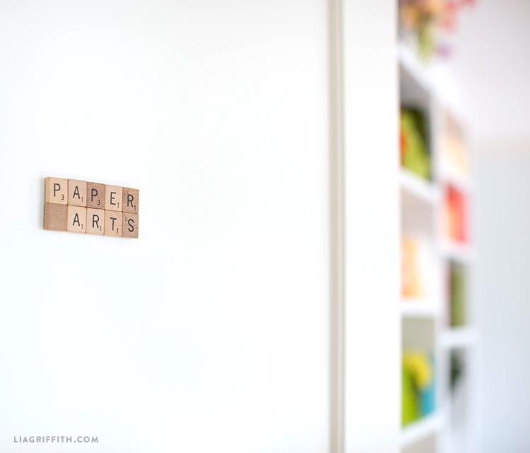 Front door of craft room with wood tiles that spell paper arts