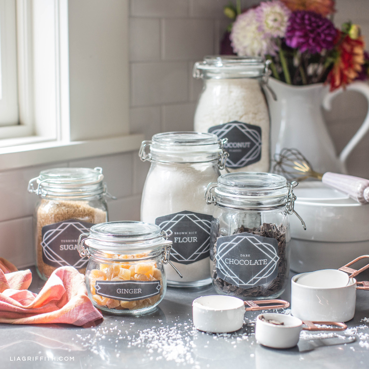 Labels for pantry jars on kitchen counter with measuring cups and vase