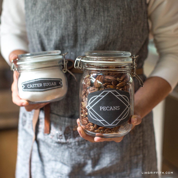 Person holding two jars with pantry labels for sugar and pecans