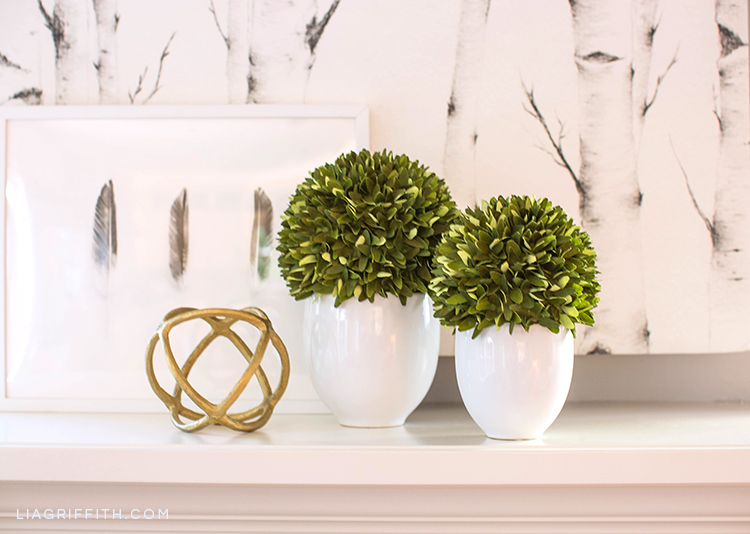Lia Griffith double-sided crepe paper boxwood topiary plants on mantel next to wall art