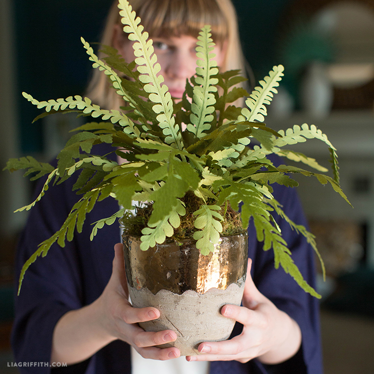 Designer holding double-sided crepe paper fern plant