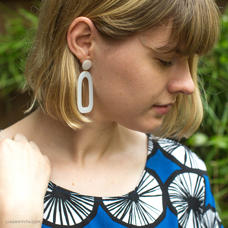 Close-up of long geometric shrink film earrings