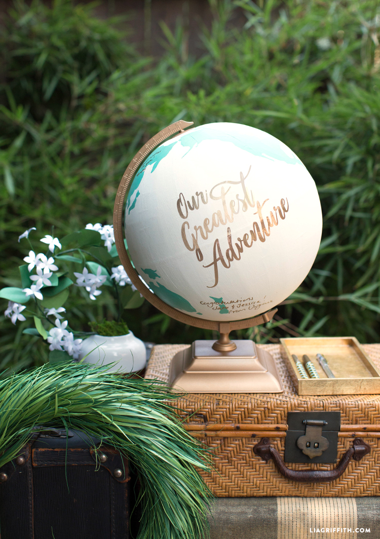 Globe guest book outside on suitcase