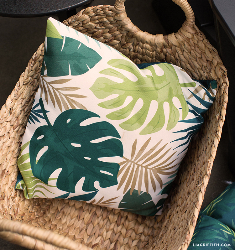 Close-up of tropical outdoor pillow in woven basket