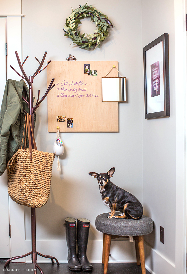 Coat rack, printable wall quote, wood dry erase board, paper fern wreath, and mid-century stool in entryway
