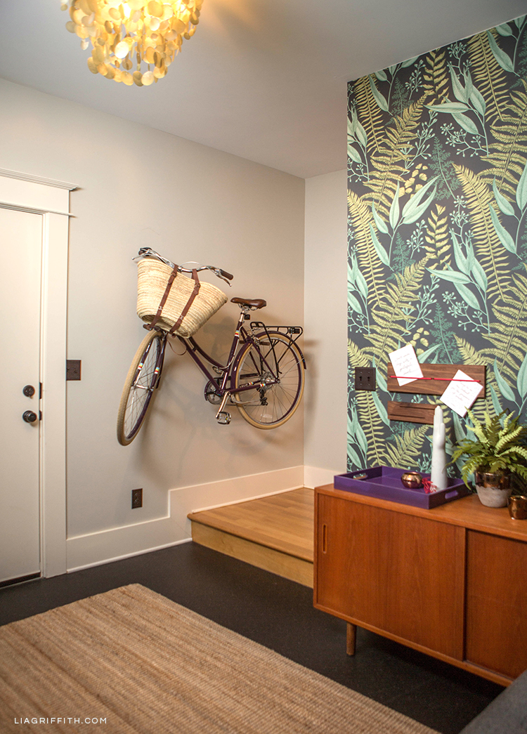 Bike rack, removable fern wallpaper, round pendant light, message board, key station, lacquer tray, and crepe paper fern plant in entryway