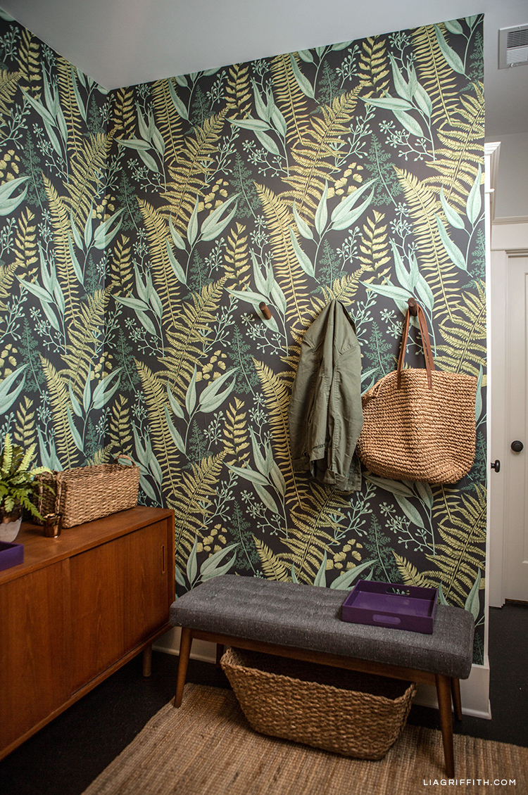 Removable fern wallpaper, wall hooks, mid-century bench, and storage baskets in entryway