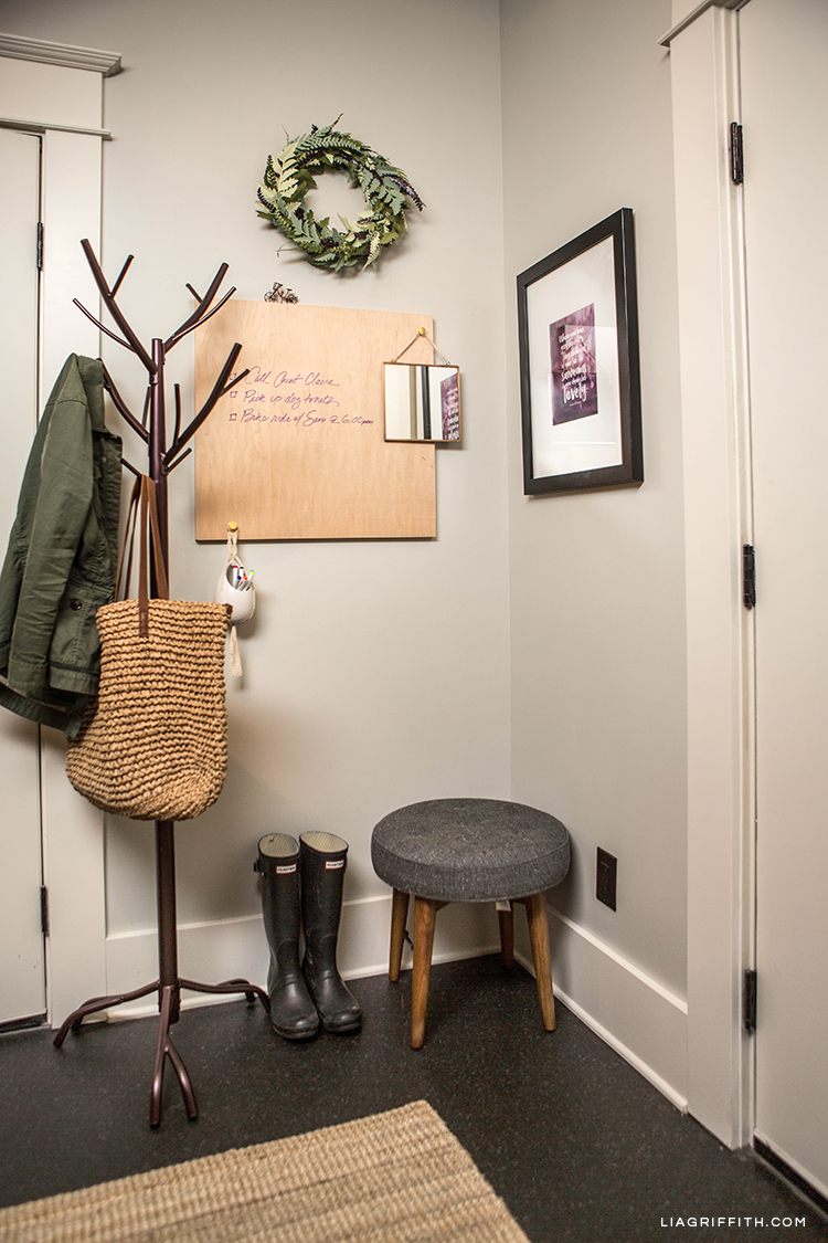 Coat rack with straw tote bag, mid-century stool, paper fern wreath, printable wall quote, wood dry erase board, and flatwoven rug in entryway