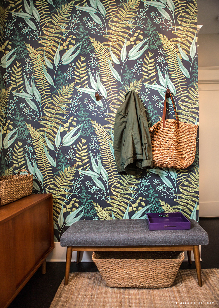 Removable fern wallpaper, wall hooks with jacket and straw tote bag, mid-century bench, and braided storage basket in entryway