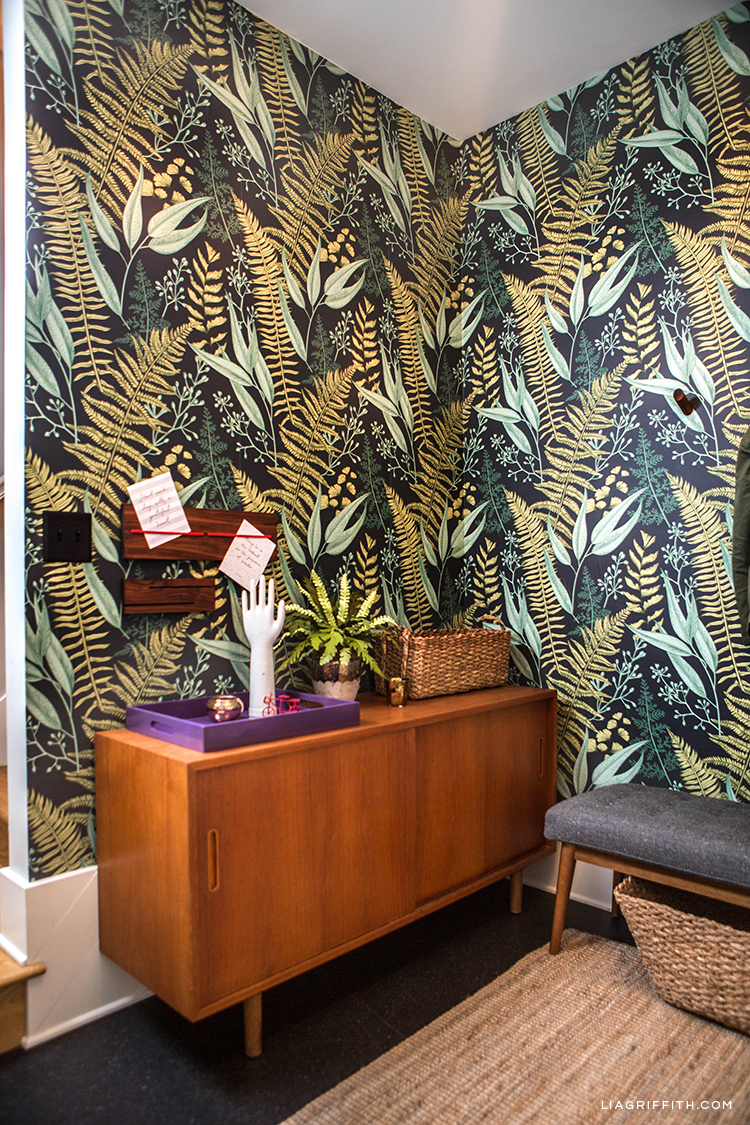 Removable fern wallpaper, lacquer tray, message board, key station, and flat woven rug in entryway