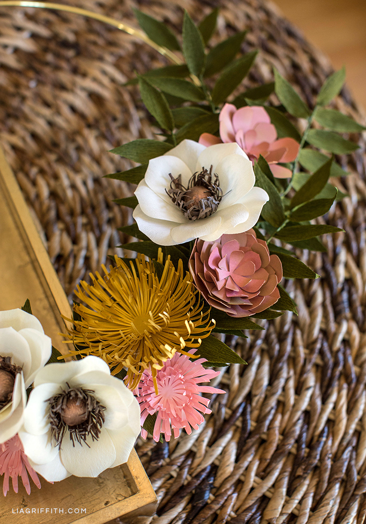 Paper flower wreath for fall with mums, anemones, succulents, and greenery on wicker table
