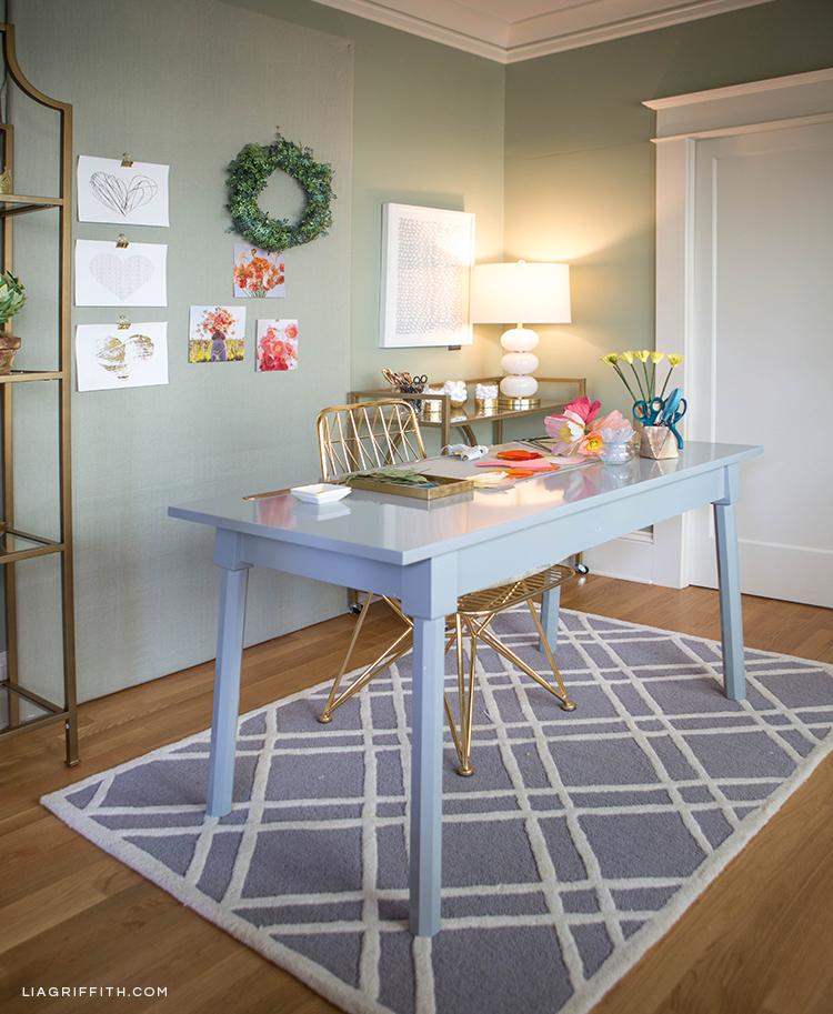Creative workspace with grey desk, gold chair, and grey area rug