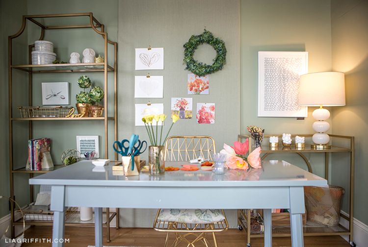 Creative workspace with grey desk, gold chair, gold craft cart, and gold etagere from Hayneedle