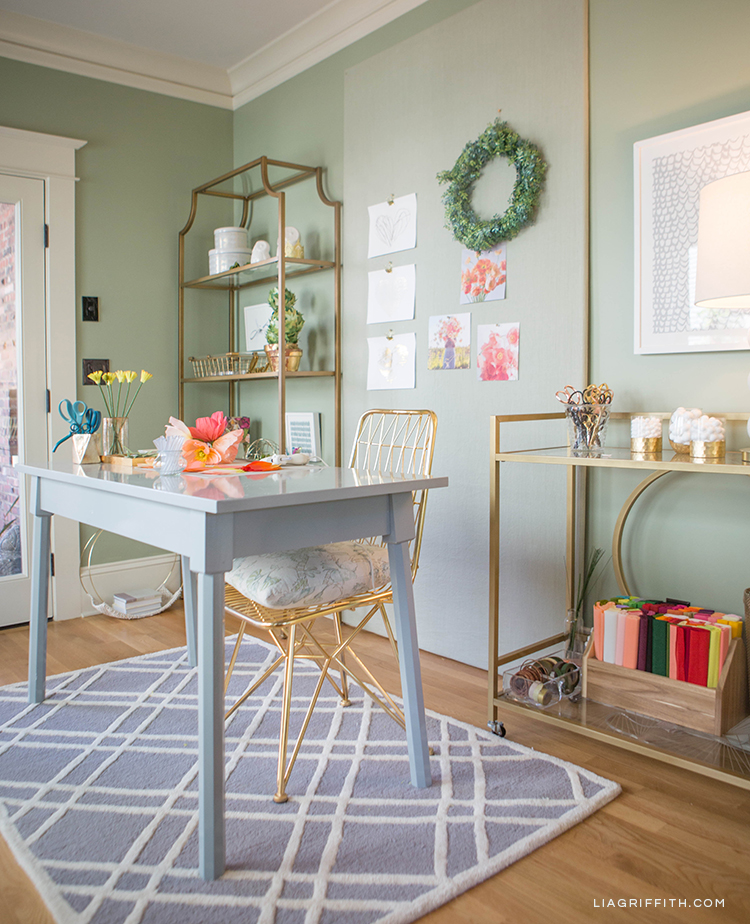 Creative home office with grey chair, grey area rug, gold chair, gold bar cart, and gold etagere from Hayneedle