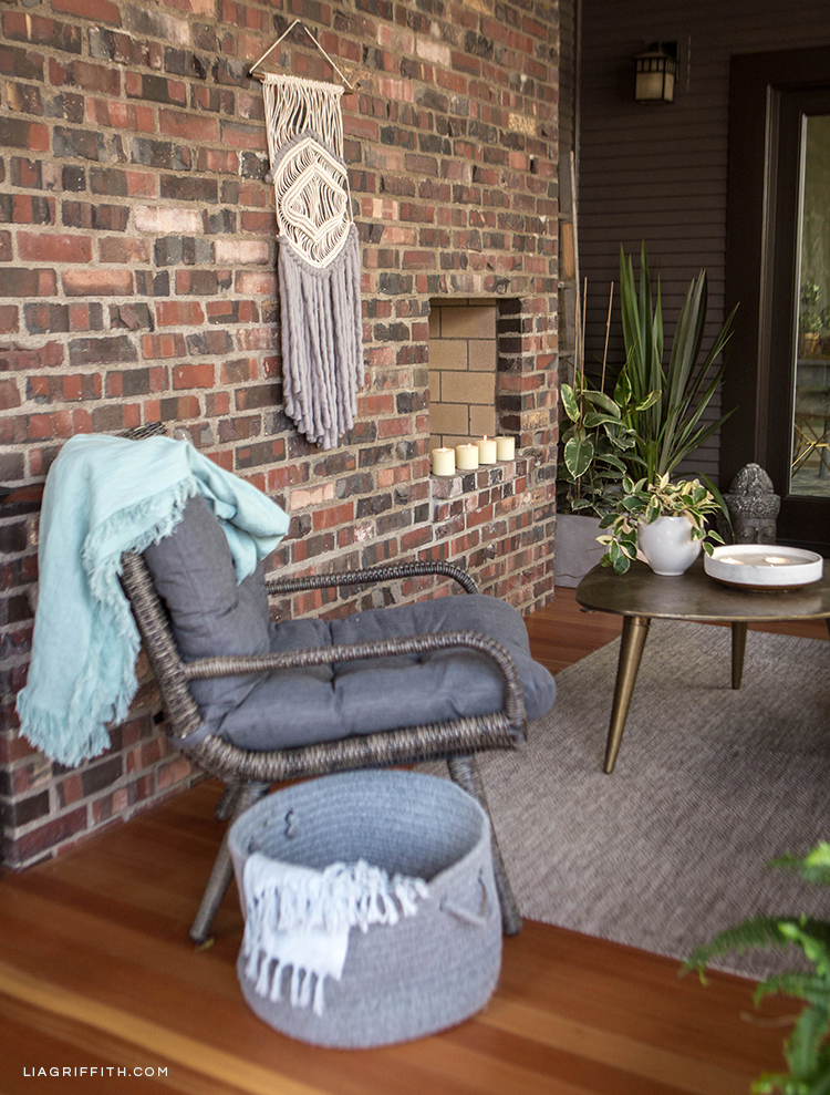 Hayneedle wicker chair with DIY linen throw, storage basket, and DIY macrame and yarn wall hanging near brick fireplace