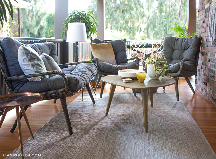 Close-up of Hayneedle wicker conversation set, cocktail table, copper side table, and indoor/outdoor area rug on porch
