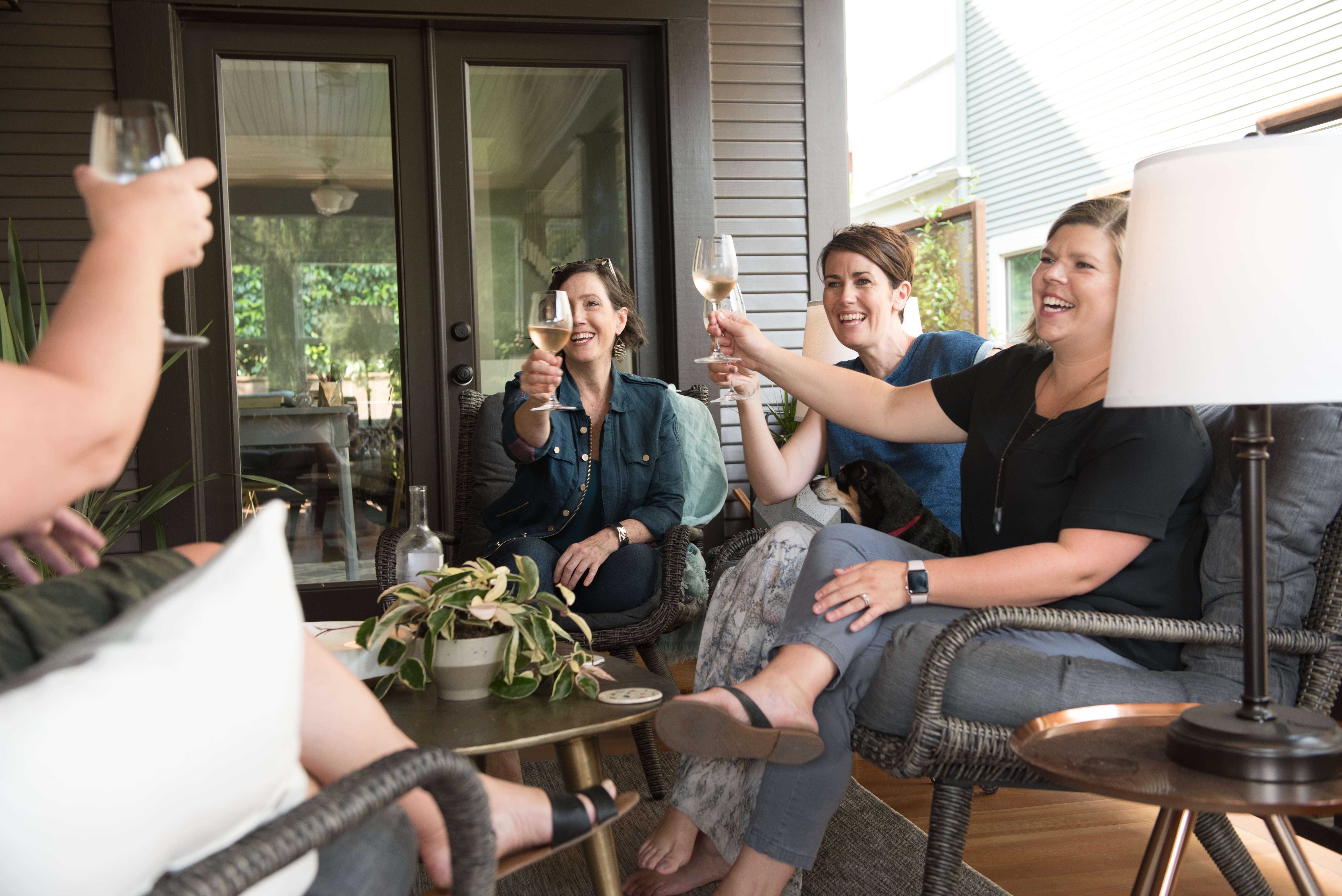 Lia Griffith team sitting on conversation set on front porch