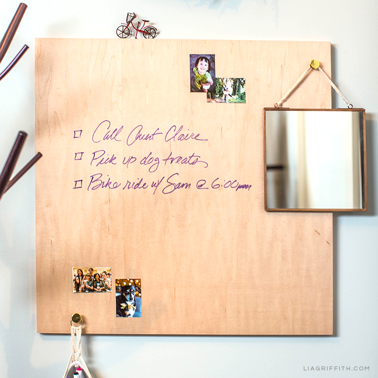 Wood dry erase board with to-do list, small mirror, and pictures