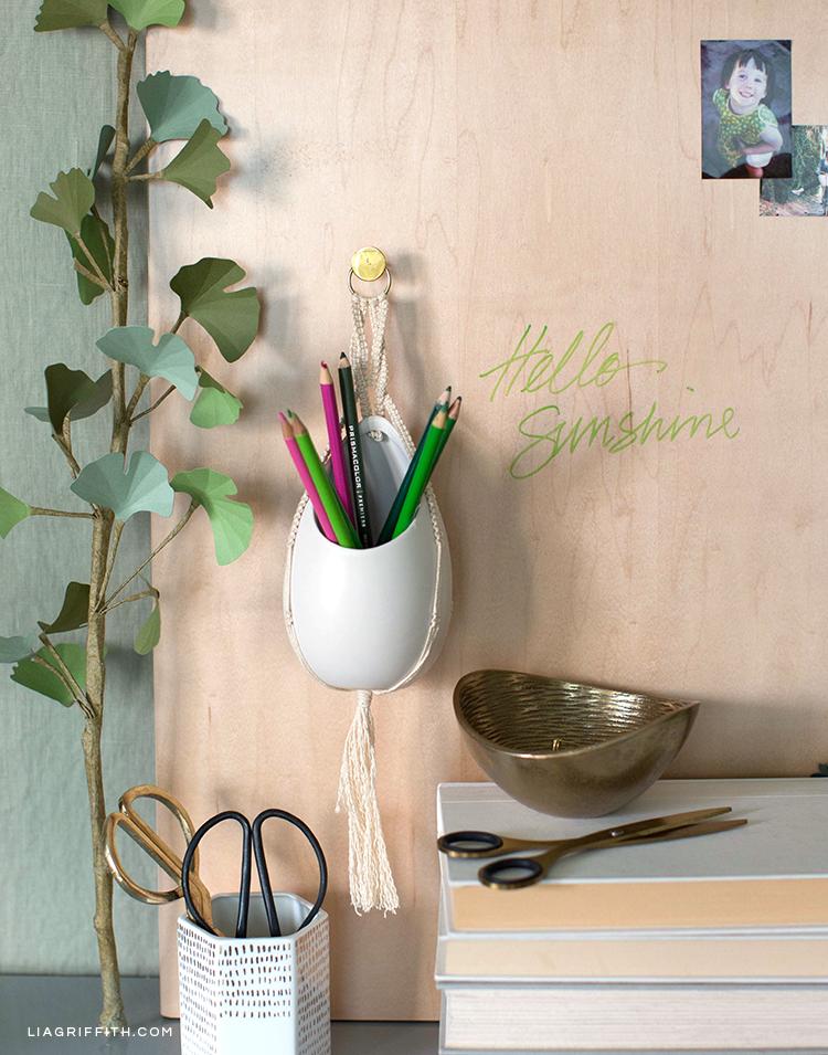Macrame pencil holder hanging on wood dry erase board above desk supplies
