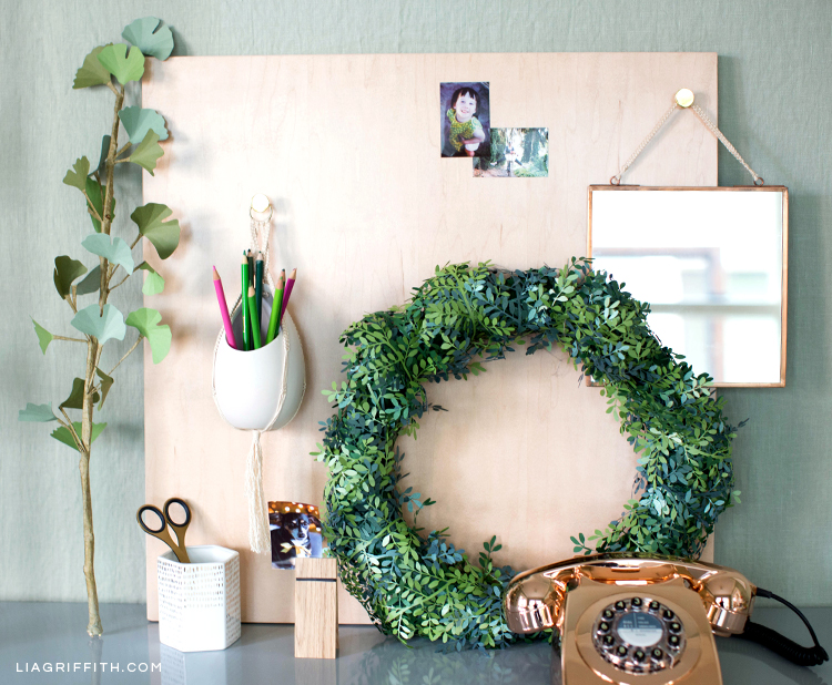 Mini macrame wall hanging on wood dry erase board with office supplies and paper wreath