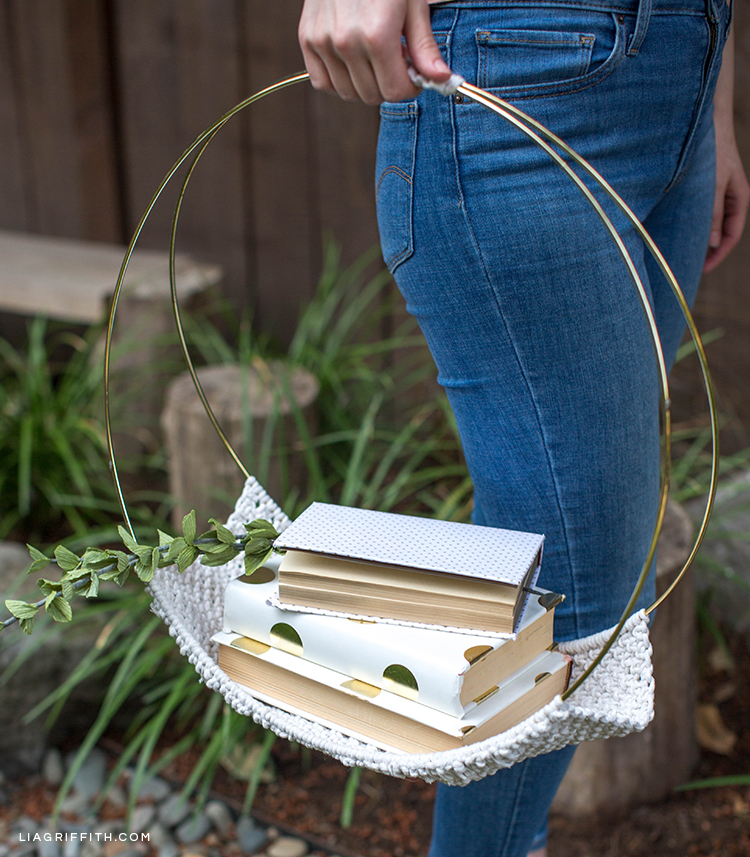 Person holding macrame magazine holder with books