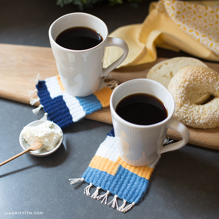 Coffee mugs on woven coasters next to bagel and butter