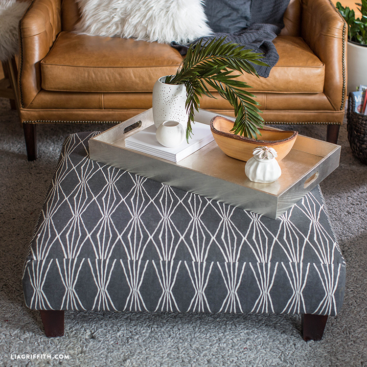 Updated ottoman with serving tray on top next to couch in living room