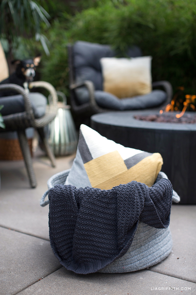 Fabric basket with pillow and blanket plus wicker seats and outdoor fire pit from Hayneedle in background